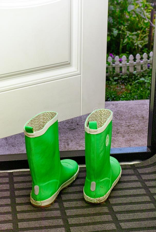 Pair of Reima child rubber boots standing indoors near open door royalty free stock photography