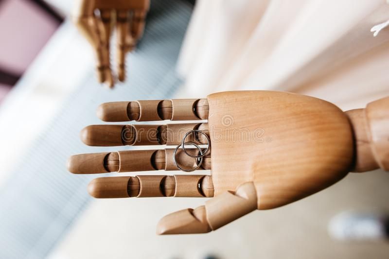 Pair of the rings is laying at the wooden mannequins hand closeup royalty free stock images