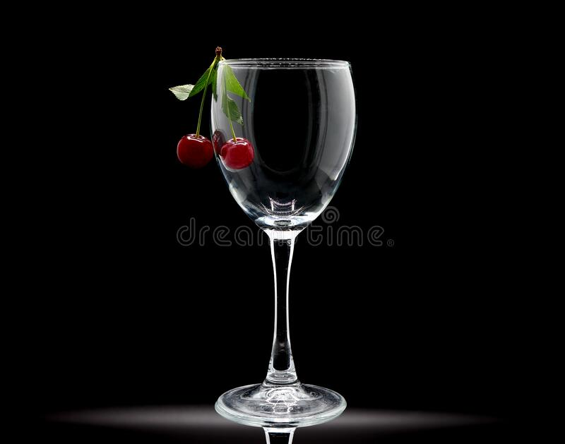 Pair of ripe cherries in an empty wine glass on a black background. royalty free stock photo