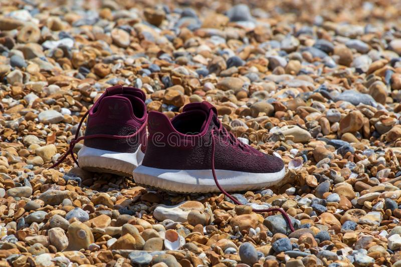 The pair of running shoes are waiting for their master at the seashore while he participates in some kind of adventures stock photo