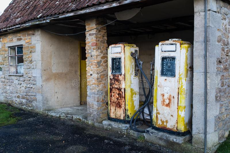 A pair of rusting old yellow petrol pump stock images