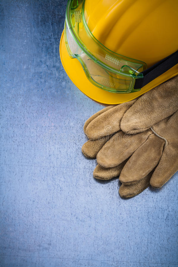 Pair of safety working gloves building helmet and transparent pr. Otective goggles on scratched metallic background construction concept royalty free stock images