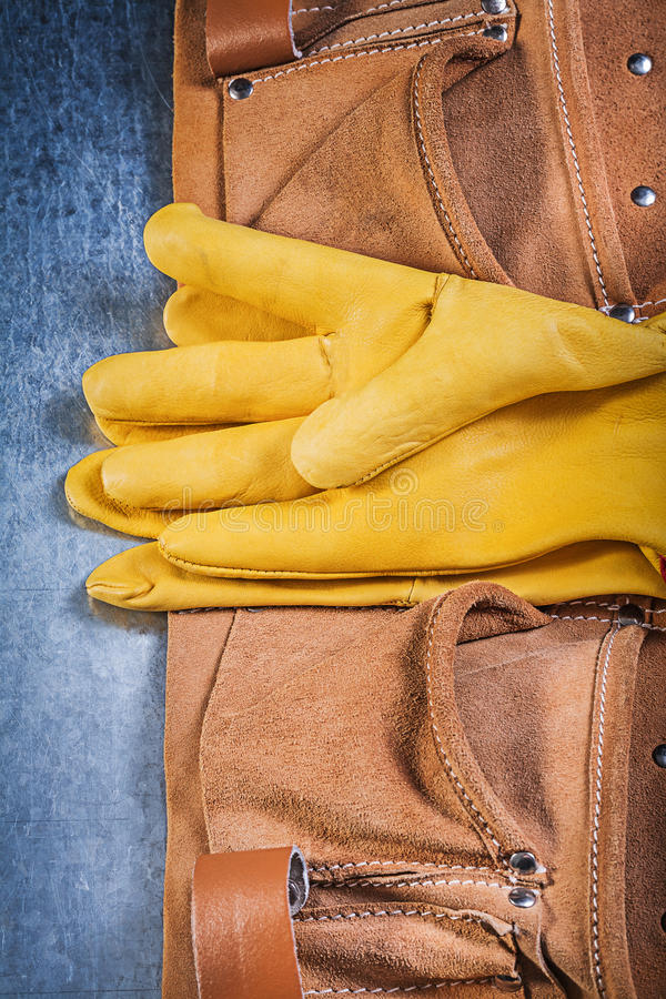 Pair of safety working gloves toolbelt. On metallic background construction concept royalty free stock photo