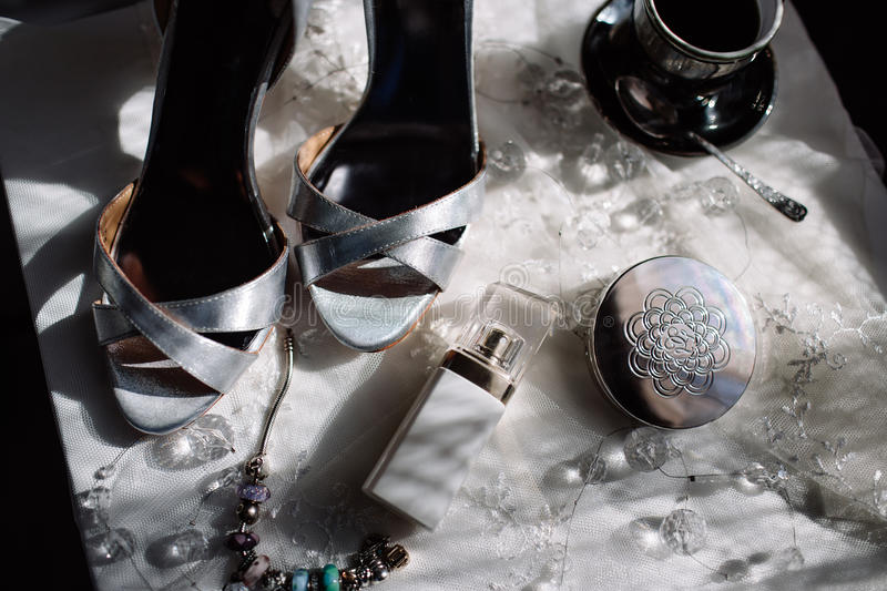A pair of shiny silver high-heeled shoes, an orchid, lipstick, perfume, a cup of coffee.  royalty free stock photos
