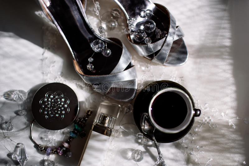 A pair of shiny silver high-heeled shoes, an orchid, lipstick, perfume, a cup of coffee.  stock image