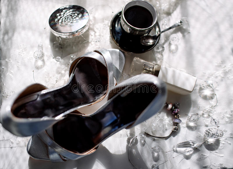A pair of shiny silver high-heeled shoes, an orchid, lipstick, perfume, a cup of coffee.  royalty free stock photography