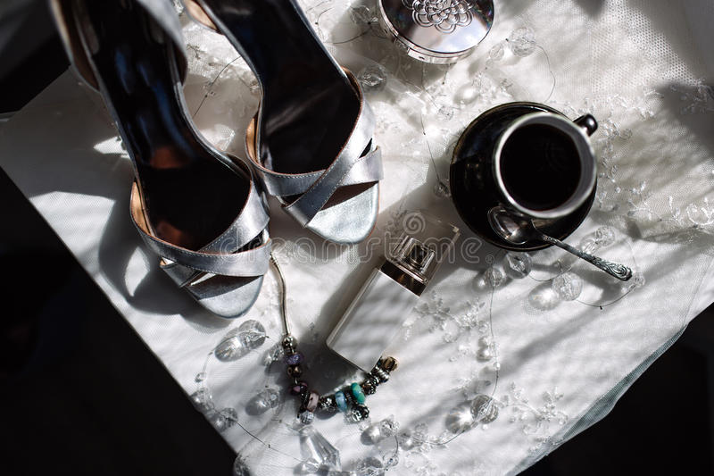 A pair of shiny silver high-heeled shoes, an orchid, lipstick, perfume, a cup of coffee.  stock images