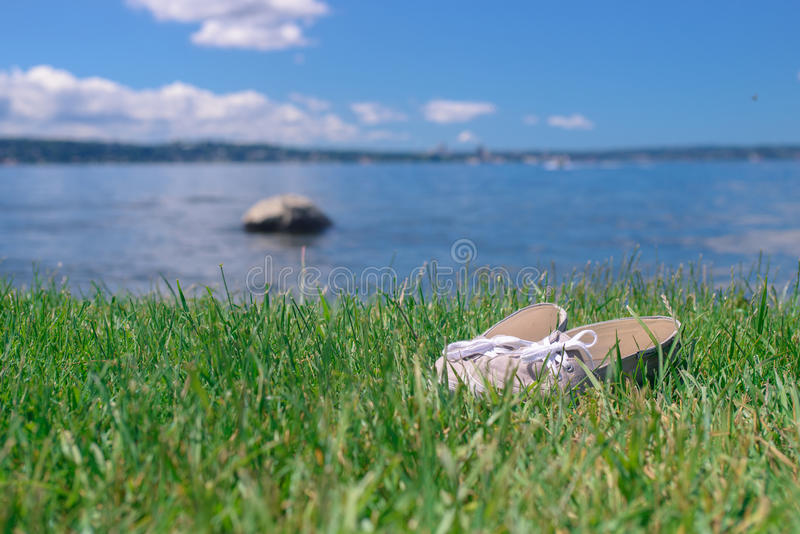 A pair of shoes in a bright green grass near the lake. Under a blue sky stock images