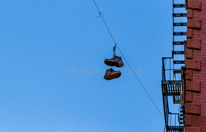 A pair of shoes hung on a wire on a street in  New York City. A pair of shoes hung high up on a wire in front of a high rise on a street in  New York City royalty free stock image