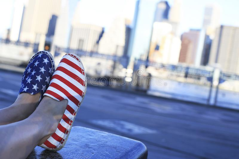 Pair of shoes painted like the American flag. On the bench stock photos