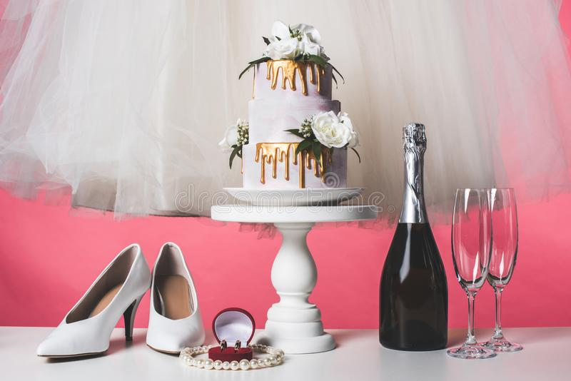 Pair of shoes, wedding cake and champagne. Isolated on pink stock photo