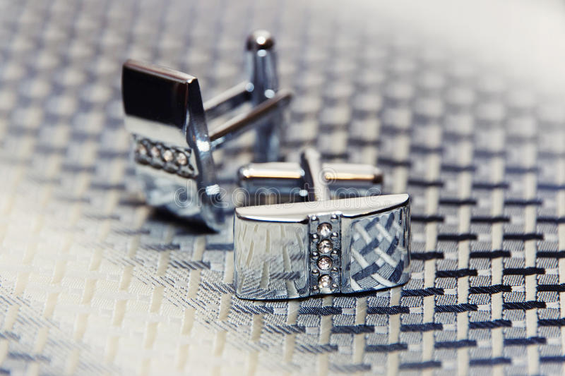 Pair of silver cuff links on the man's tie. Pair of silver cuff links on the tie stock image