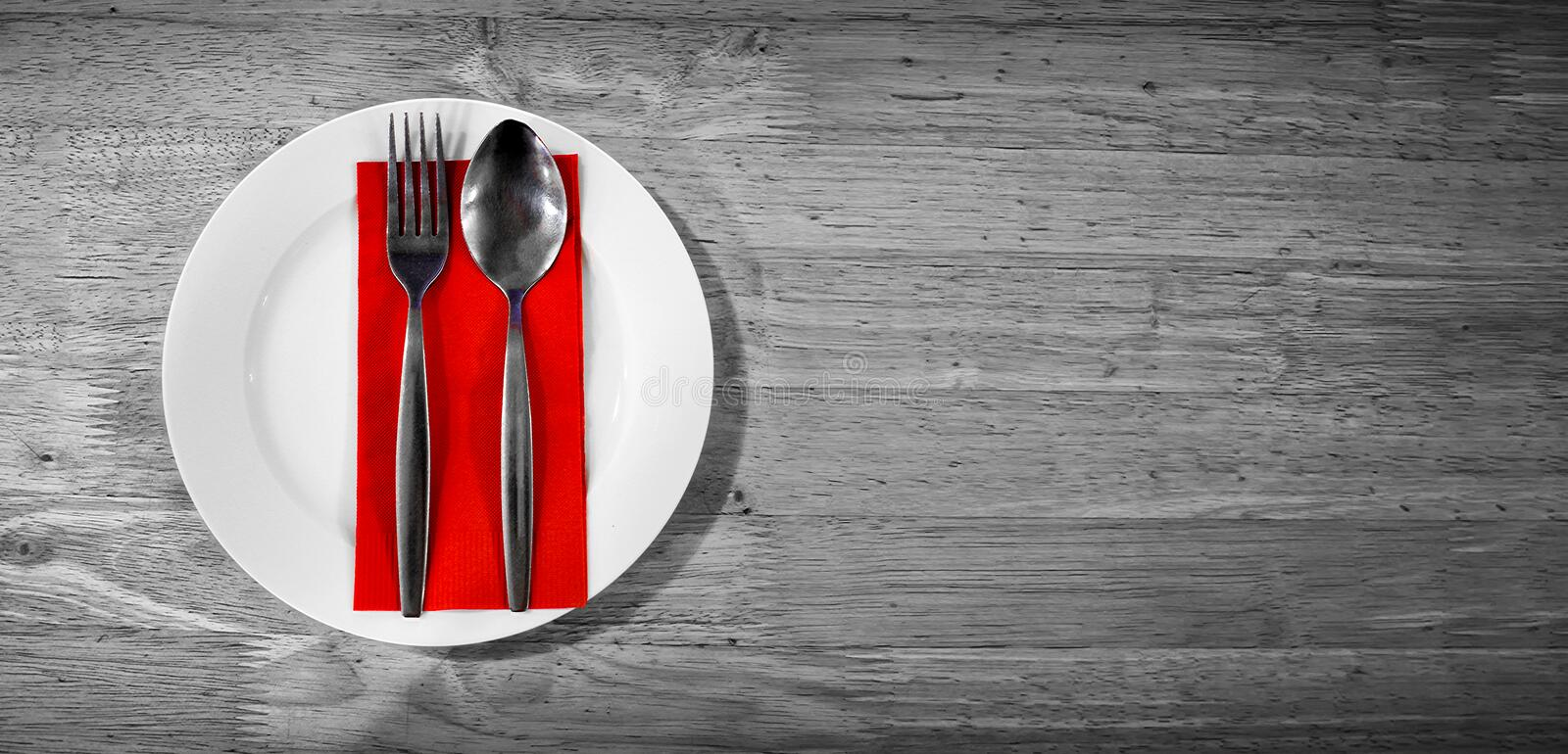 Pair of Silver Spoon and Fork on a Red Napkin on a Grey Surface. stock photo