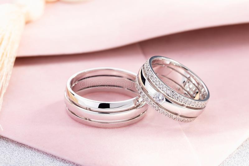 Pair of silver wedding rings with diamonds on female ring lies on pastel pink background stock photography