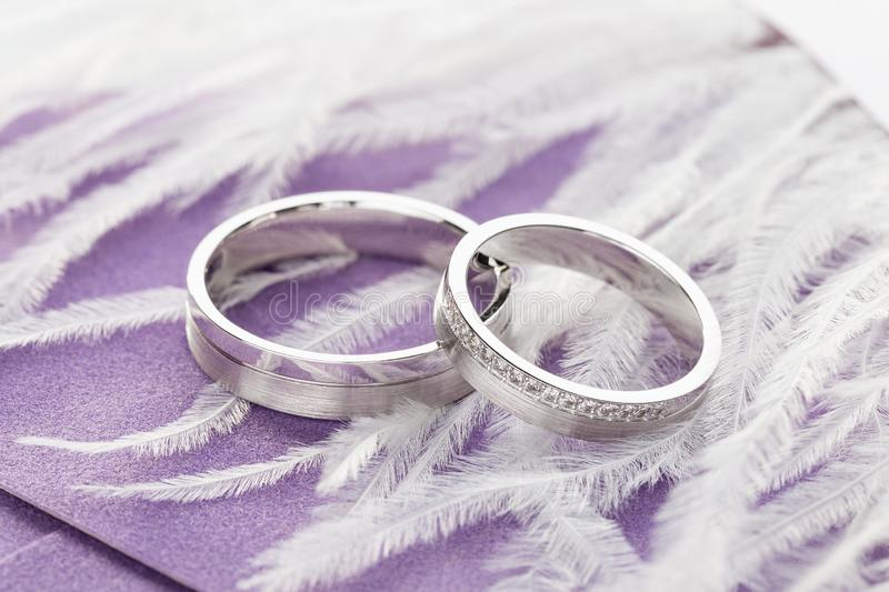 Pair of silver wedding rings with diamonds on purple background with feathers royalty free stock image