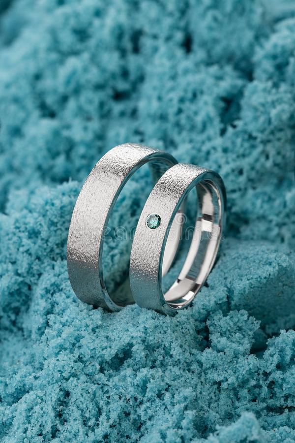 Pair of silver wedding rings with textured surface and blue gemstone in female ring on turquoise sand background royalty free stock images