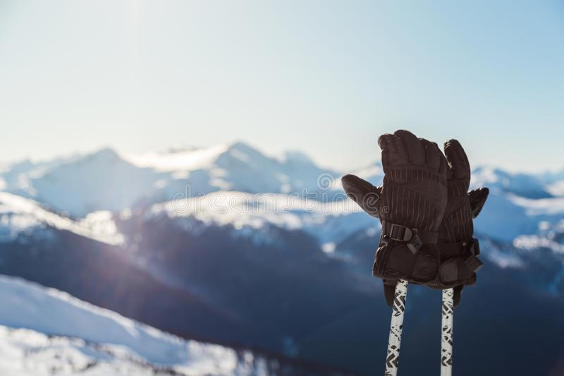 A pair of ski gloves on poles with snowy mountain peaks in the background on a sunny day. stock photos