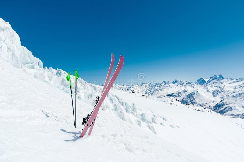 A pair of skis and ski poles stick out in the snow on the mountain slope of the Caucasus against the backdrop of the. Caucasian mountain range and the blue sky royalty free stock images