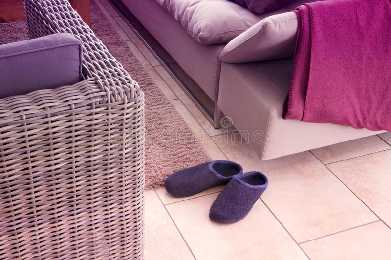 Pair of slippers next to a couch stock photos
