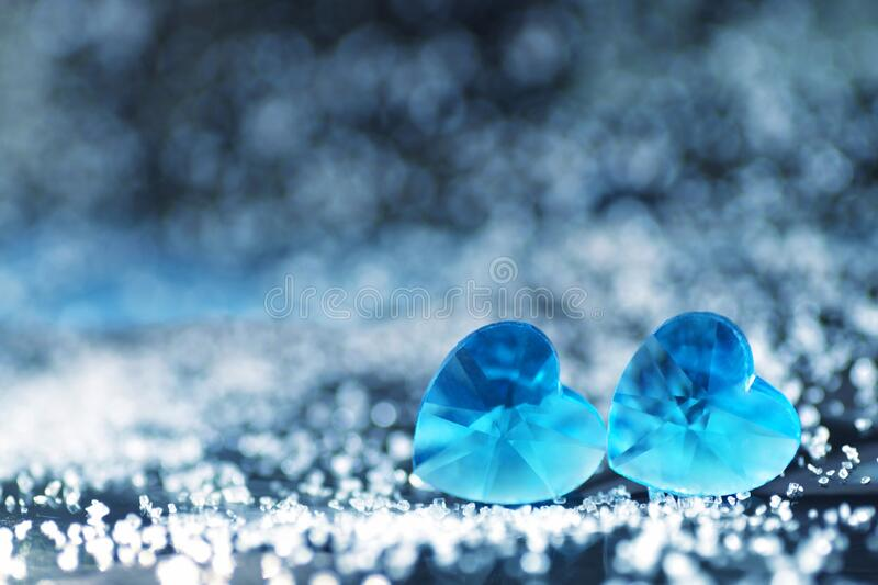 A pair of small blue plastic hearts lying next to each other with beautiful silver bokeh effects and a copy space for text. Valentines day card stock photography