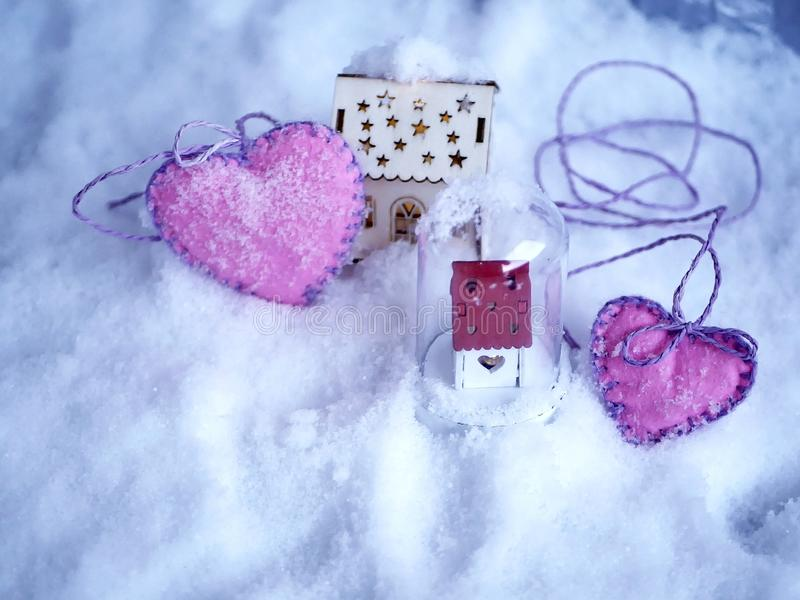 A pair of small toy houses with lighted illumination and a pair of pink hearts of felt on the snow. The concept of seasonal winter holidays, Valentines day stock photos