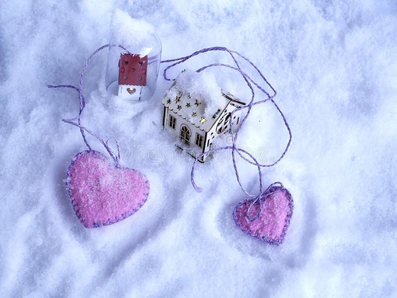 A pair of small toy houses with lighted illumination and a pair of pink hearts of felt on the snow. The concept of seasonal winter holidays, Valentines day stock photography