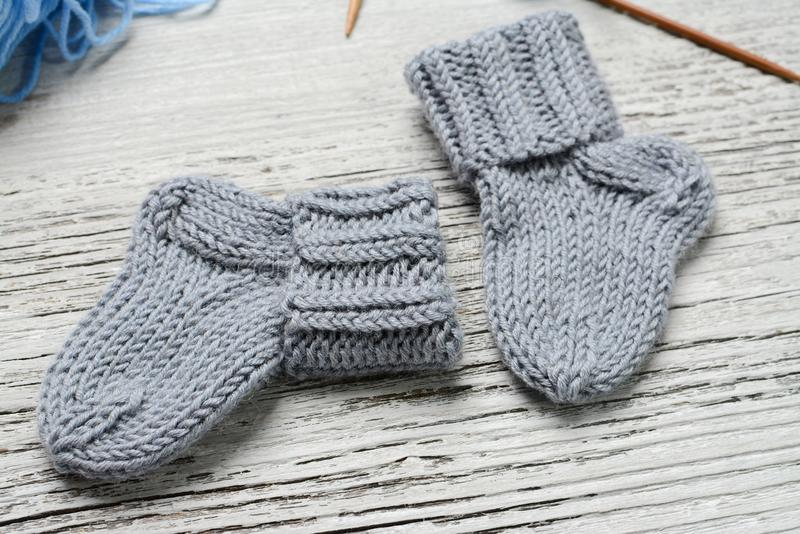 Pair of small woolen socks for newborn on wooden vintage table. Handmade for tiny baby feet royalty free stock photography