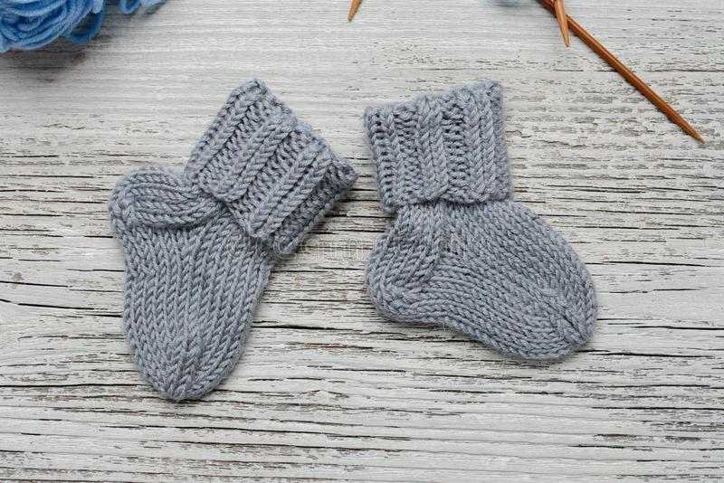 Pair of small woolen socks for newborn on wooden vintage table. Handmade for tiny baby feet stock images