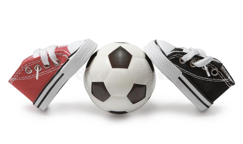 A pair of sneakers of different colors are leaning on a soccer ball. stock images