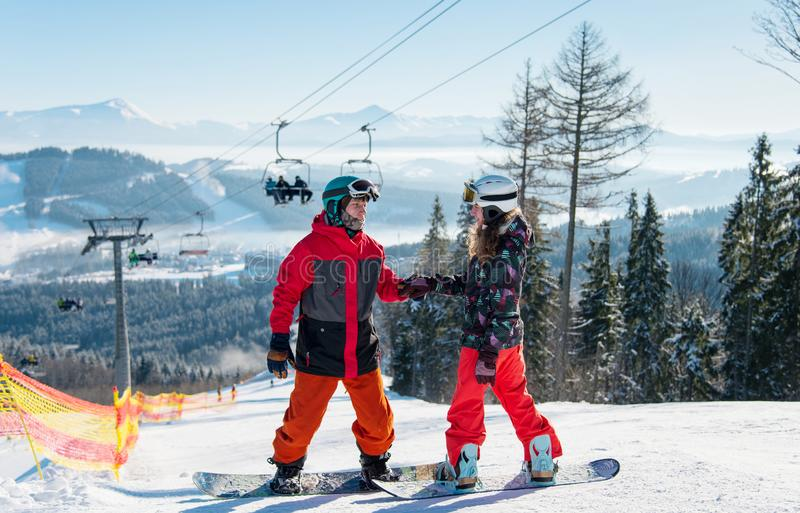 Pair of snowboarders on top of a ski slope at winter resort downhill on a sunny day. Man holds a woman`s hand against the backdrop of a ski-lift and snow royalty free stock photography