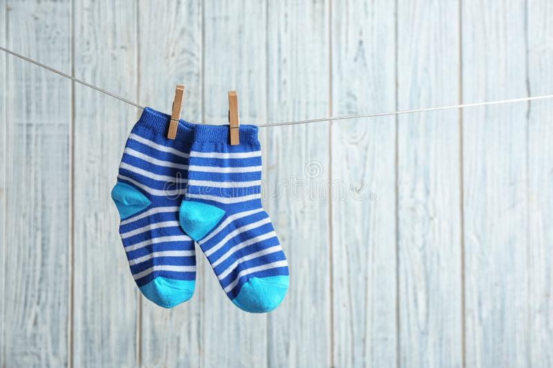 Pair of socks on laundry line against wooden background. Baby accessories royalty free stock photo