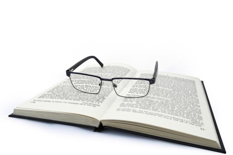 Pair of spectacles, glasses on black hard back book with text stock images