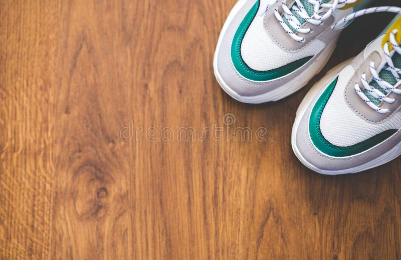 Pair of sport shoes on wooden background. New sneakers and space for ad text stock images