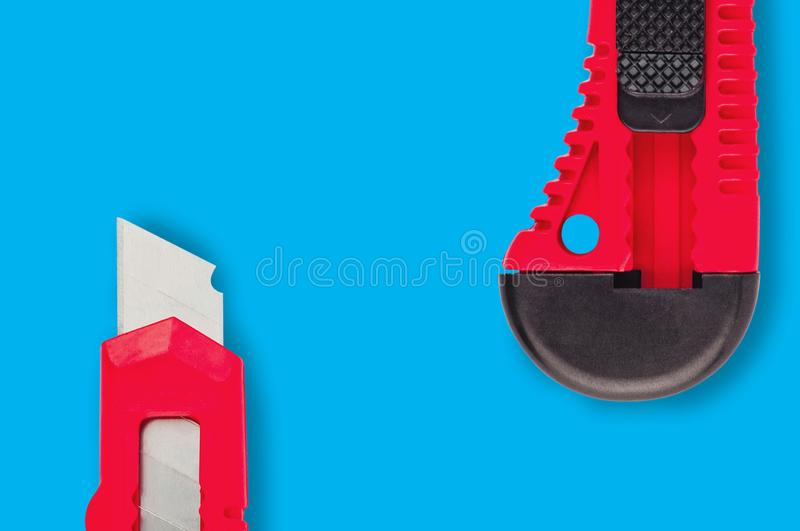 Pair of stationery knives with red plastic handle on blue background royalty free stock photos