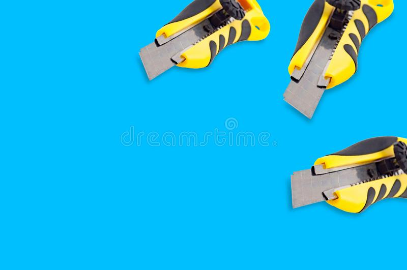 Pair of stationery knives with yellow and black plastic handle on blue background royalty free stock photo