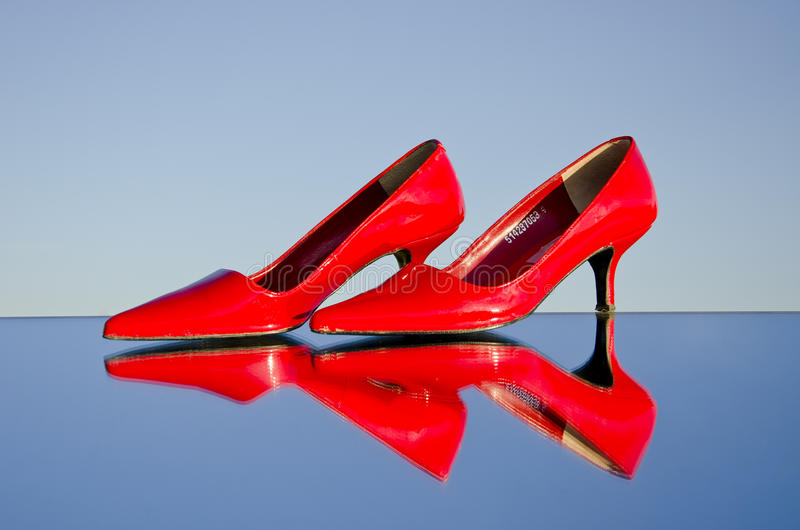 A pair of stiletto on mirror. A pair of red stiletto on mirror and sky background stock image