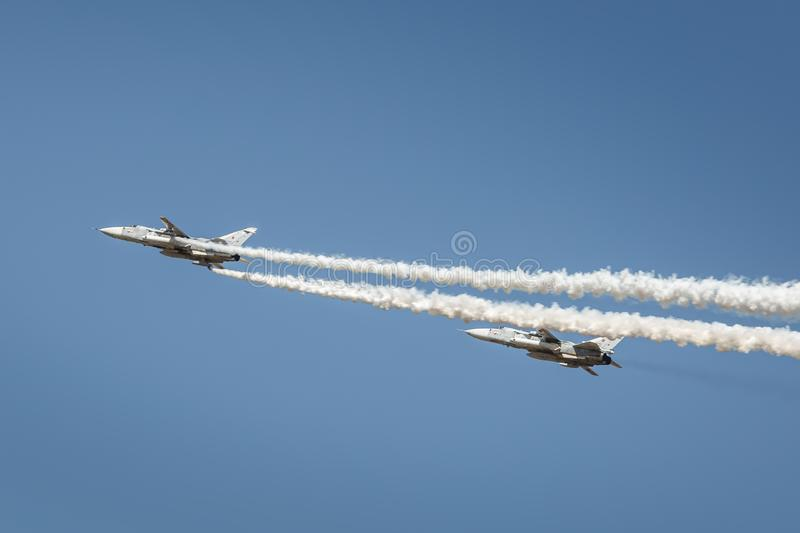 A pair of SU-24 aircraft perform demonstration flights in the sky over a military training ground royalty free stock image
