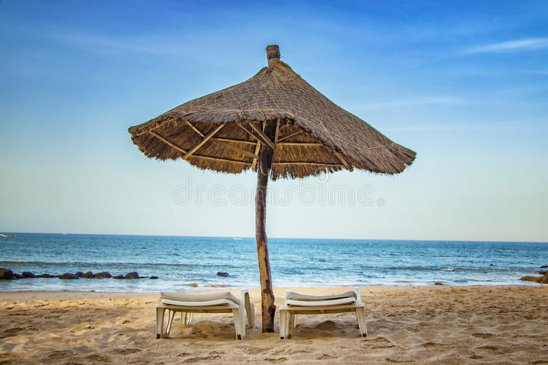 Pair of sunbed with parasol on beautiful empty beach near clear sea. It is a tropical paradise in Africa, Senegal. There is blue. Sky. It is the right place to stock photos