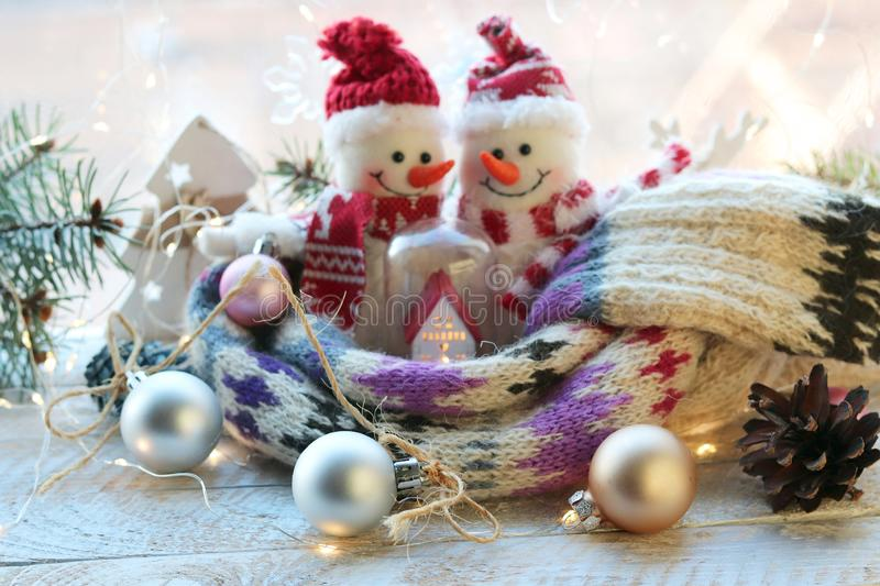 A pair of toy snowmen, a house, a scarf, Christmas decor, illuminations on a wooden surface on a window background royalty free stock images