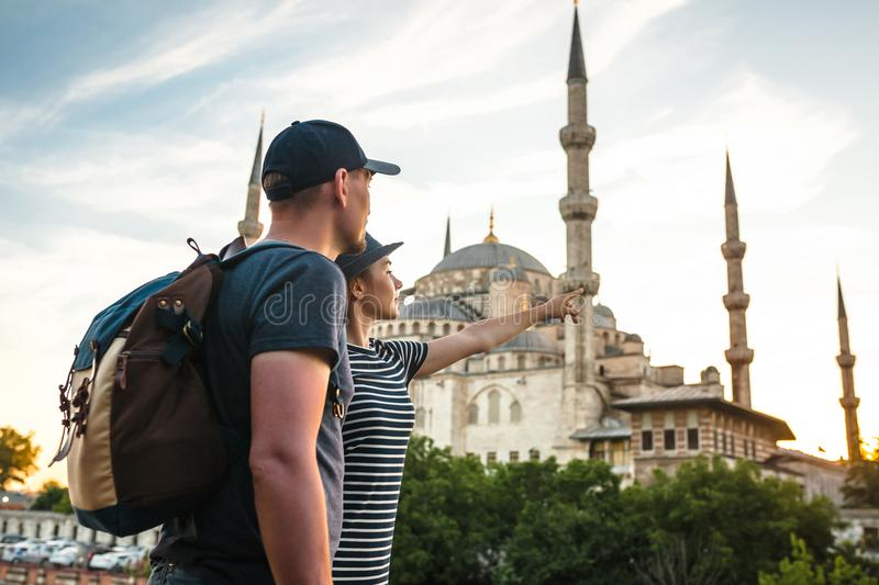 A pair of travelers near the world-famous Blue Mosque in Istanbul, Turkey. The girl shows direction. stock images