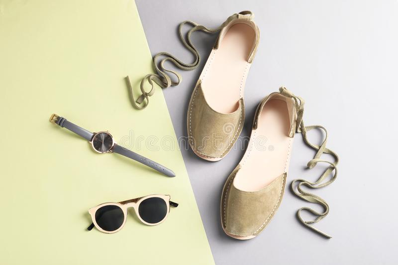 Pair of trendy women`s shoes and accessories. On color background stock photography