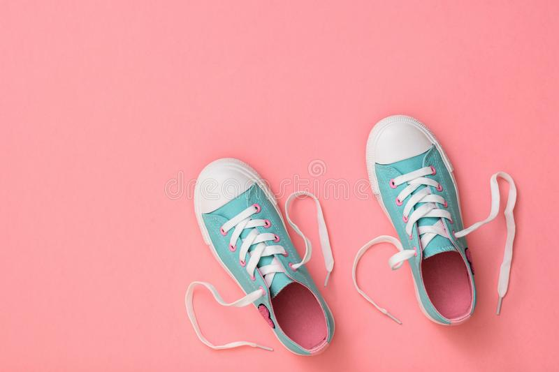 A pair of turquoise sneakers with laces on a pink background. Color trend 2019. Sports style. Flat lay. The view from the top royalty free stock image