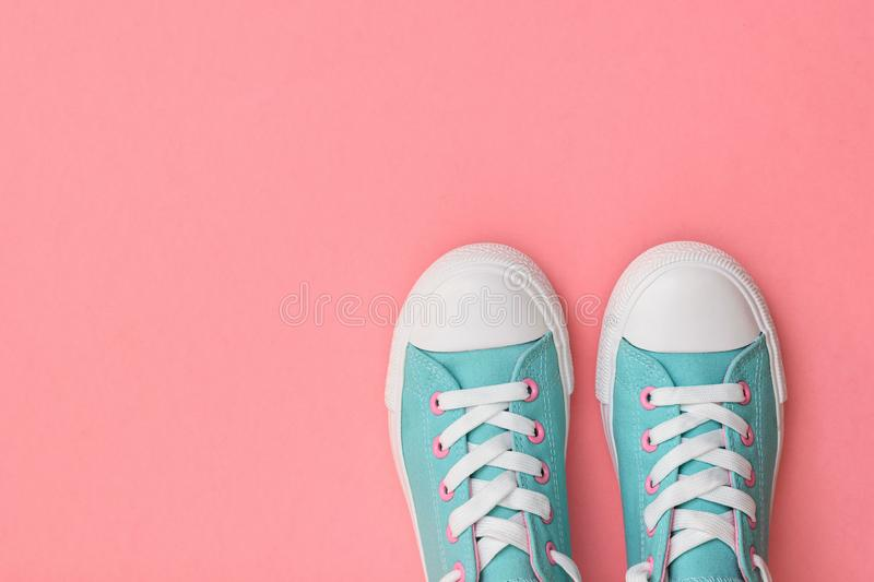 A pair of turquoise sneakers on a pink background. Color trend 2019. Sports style. Flat lay. The view from the top royalty free stock image