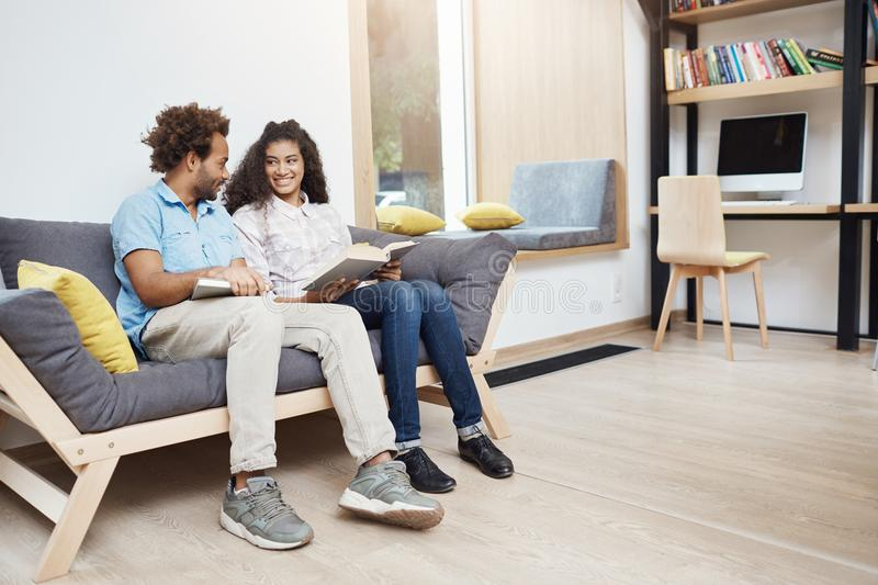 Pair of two dark-skinned multi ethnic people on a date in library. Couple sitting on sofa, reading favourite books stock images