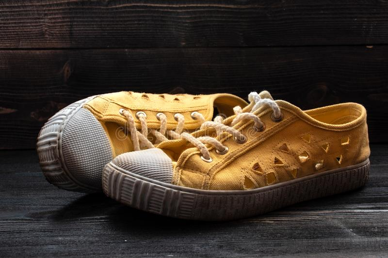 Pair of used old fashioned sneakers shoes on dark wooden surface royalty free stock images