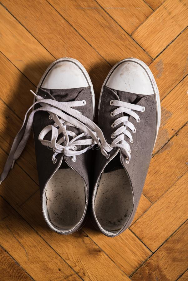 A pair of used sneakers. On the floor stock photo
