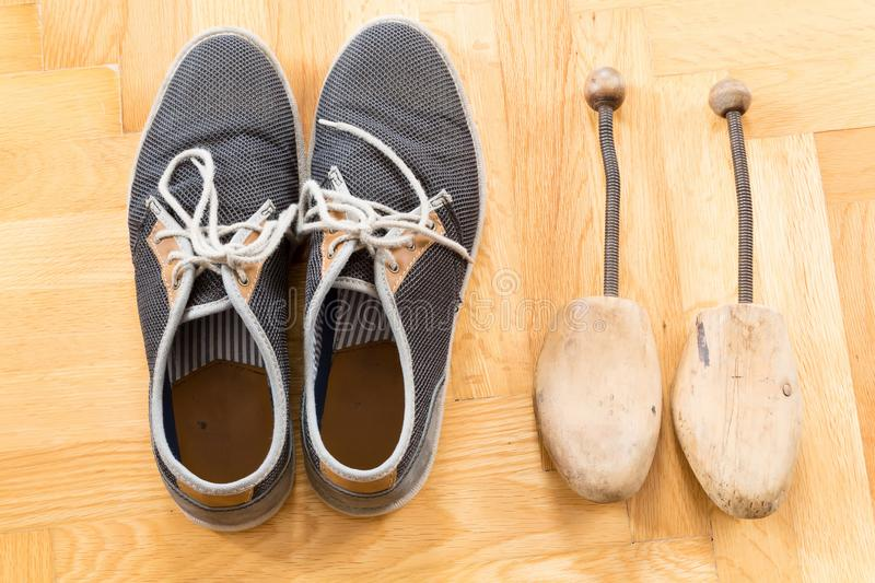 A pair of used sneakers. With shoe stretcher on the floor stock image