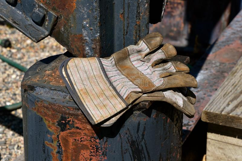 Pair of industrial work gloves. A pair of used work gloves are left on a heavy metal machine in an industrial setting royalty free stock photo