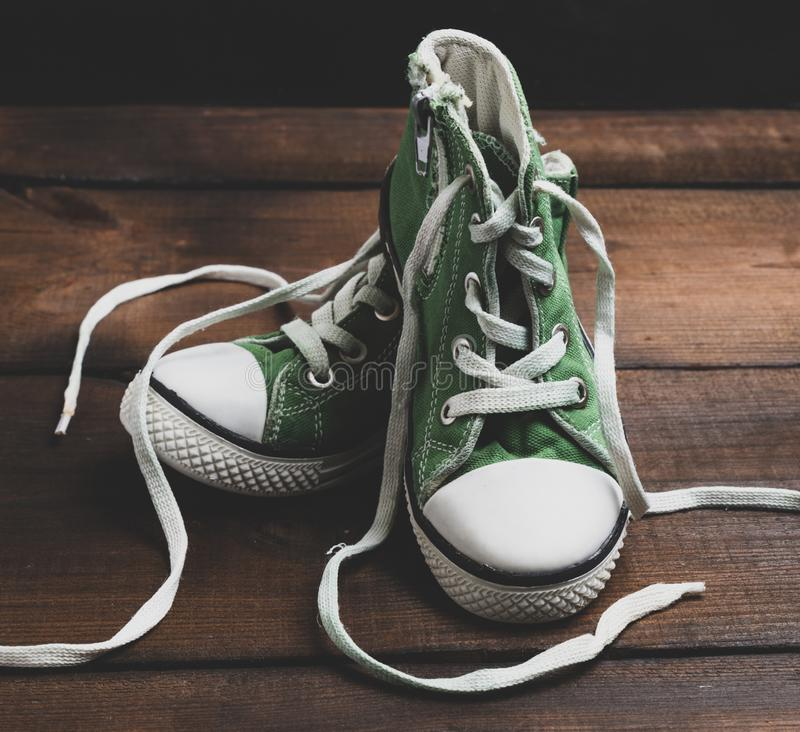 Pair of very worn green textile shoes. Stand on a brown wooden surface, vintage toning stock images