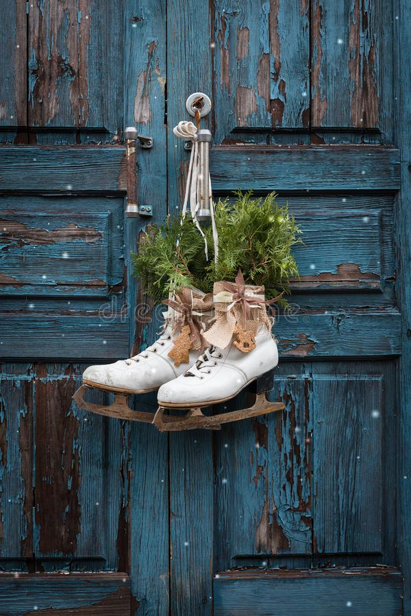 Pair of vintage white Ice Skates with Christmas decoration hanging on the blue rustic door. Toned stock image